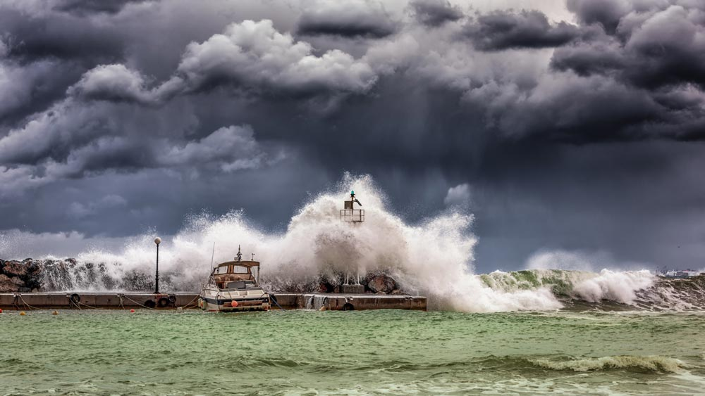Wave crashing against a harbour in stormy weather